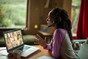Woman has web conversation with group. Wearing a headset.